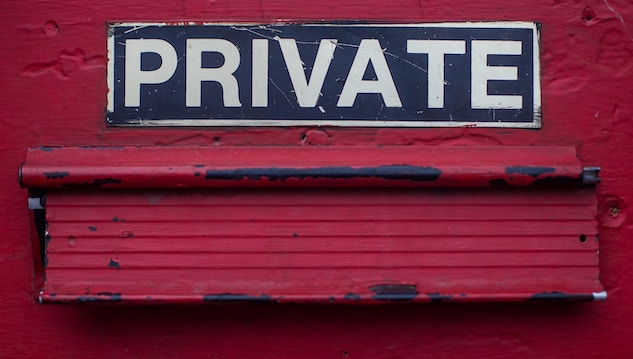 Private above red door mail slot.
